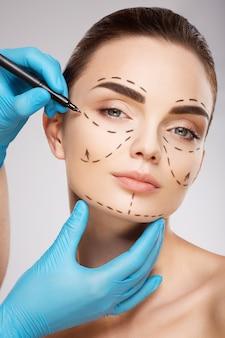 Милая девушка с темными бровями на фоне студии, руки доктора в синих перчатках, рисуя линии перфорации на лице, концепция пластической хирургии.