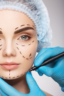 Lovely girl with dark eyebrows wearing blue medical hat at studio background, doctor's hands wearing blue gloves drawing perforation lines on face, plastic surgery concept.
