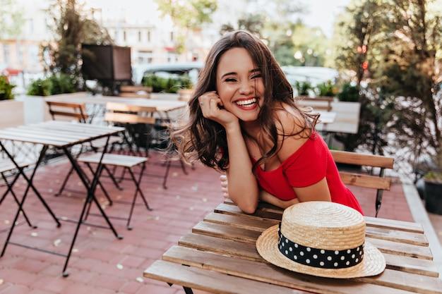 カフェに座って良い一日を楽しんでいる黒髪の素敵な女の子。屋外レストランで時間を過ごすエレガントな女性モデル。