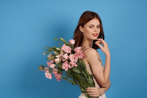 明るい青の背景に繊細なトルコギキョウの花を持つ素敵な女の子