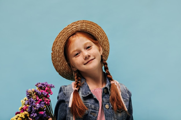 Lovely girl with freckles and red hairstyle in cool hat, denim jacket and striped shirt holding multi-colored flowers on isolated wall