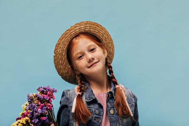 Bella ragazza con le lentiggini e l'acconciatura rossa con cappello alla moda, giacca di jeans e camicia a righe con fiori multicolori sulla parete isolata