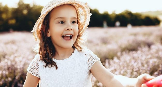 Милая девушка в шляпе гуляет и улыбается в лавандовом поле в солнечный день