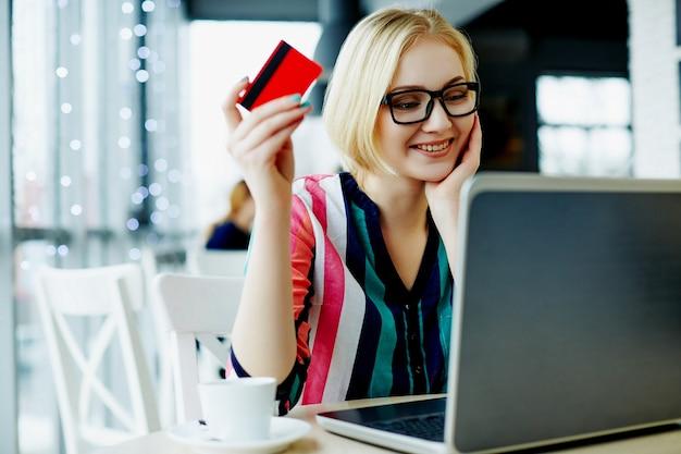 화려한 셔츠와 노트북 및 신용 카드, 프리랜서 개념, 온라인 쇼핑 카페에 앉아 안경을 쓰고 가벼운 머리를 가진 사랑스러운 소녀.