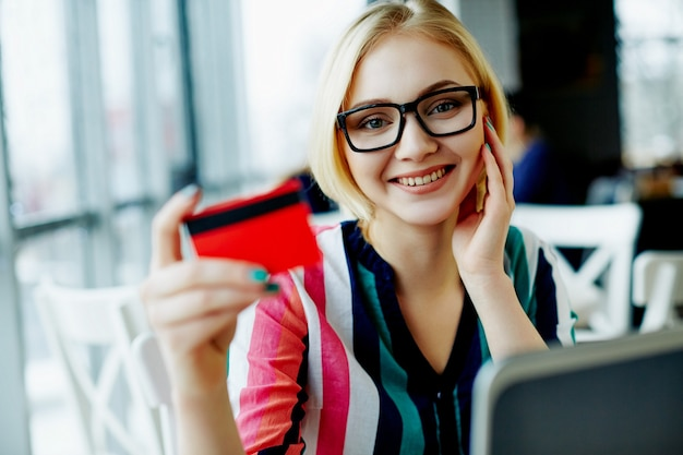 Lovely girl with light hair wearing colorful shirt and glasses sitting in cafe with laptop and credit card, freelance concept, online shopping.