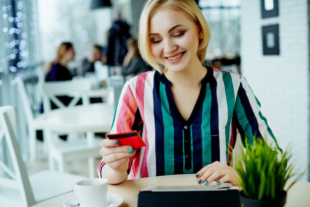Lovely girl with light hair wearing colorful shirt sitting in cafe with tablet, credit card and cup of coffee, freelance concept, online shopping.