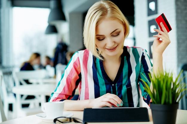 태블릿, 신용 카드 및 커피 한잔, 프리랜서 개념, 온라인 쇼핑 카페에 앉아 화려한 셔츠를 입고 가벼운 머리를 가진 사랑스러운 소녀.