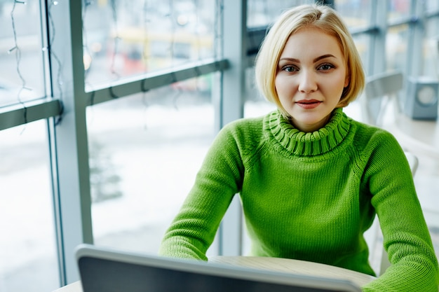 Lovely girl with light hair wearing green sweater sitting in cafe with laptop, portrait, freelance concept, online shopping.