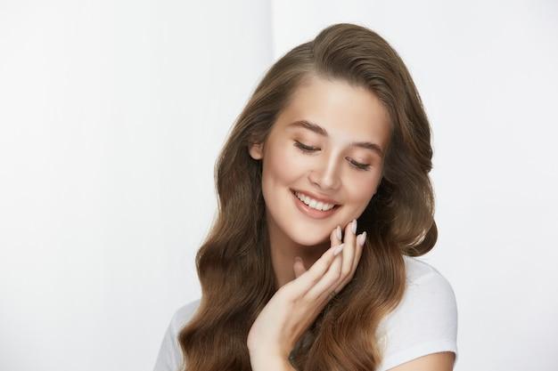 Милая девушка со светлым муа и длинными вьющимися волосами, касаясь щек и улыбаясь