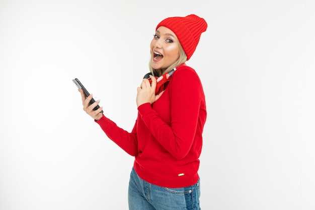 Lovely girl with a phone in her hands and red headphones on her neck on a white background with copy space