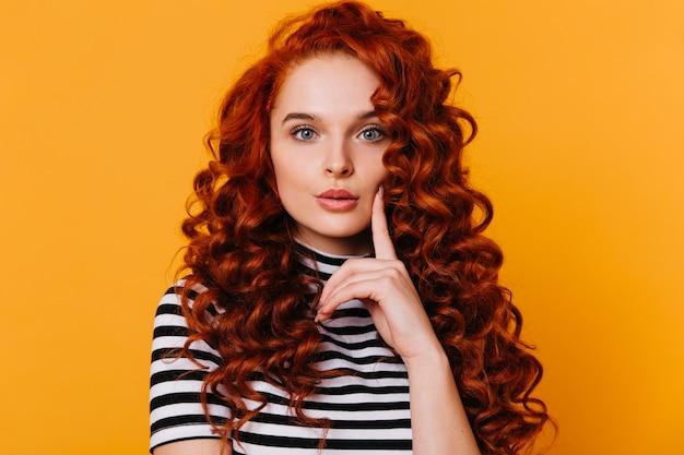붉은 곱슬 머리와 파란 눈을 가진 사랑스러운 소녀는 그녀의 손가락으로 그녀의 뺨을 만지고 격리 된 주황색 공간에서 카메라를 신중하게 바라 봅니다.