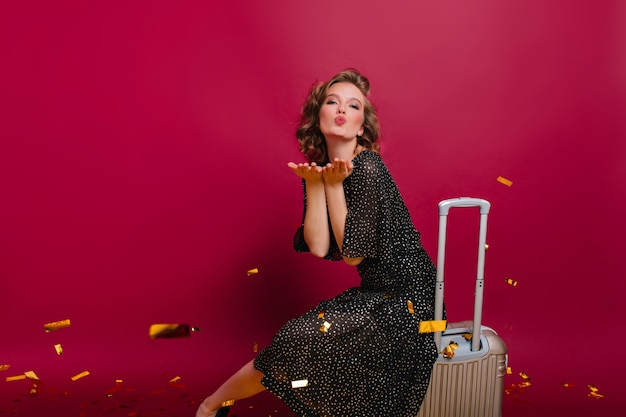 Милая девушка с короткой элегантной прической шлет воздушные поцелуи, сидя на чемодане