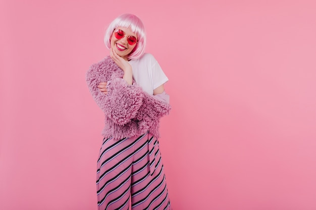 Lovely girl with short pink hair laughing with eyes closed. refined young lady wears peruke and trendy glasses during photoshoot
