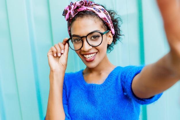 Милая девушка со стильной прической делает автопортрет камерой на бирюзе