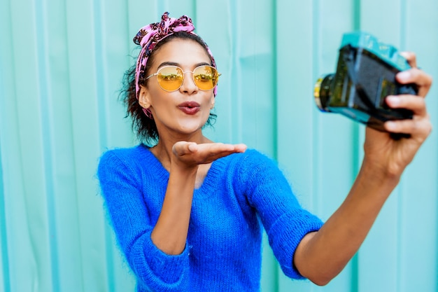 Lovely  girl with stylish hairstyle making self portrait by  camera on turquoise