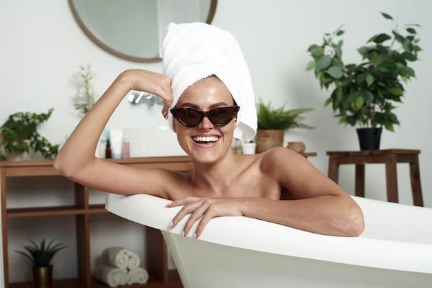 Милая девушка с витилиго улыбается белоснежной улыбкой и сидит в ванной. стильная женщина в полотенце на голове и солнцезащитных очках принимает спа-процедуры дома или в отеле.