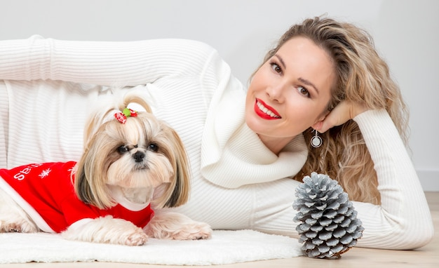 A lovely girl with a well-groomed and nicely dressed shih tzu puppy for christmas