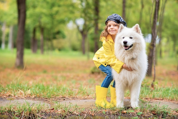Lovely girl in yellow rubber boots and rain coat on a walks, plays with a beautiful white samoyed dog in the autumn park