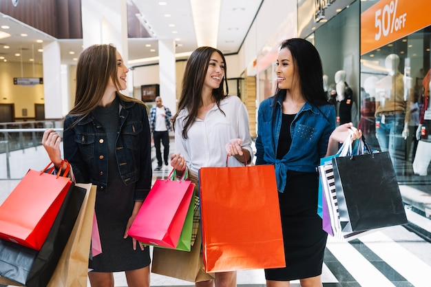 Lovely girls shopping together in mall