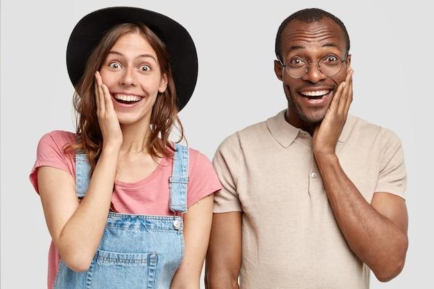 Прекрасная рада, довольная женщина и его мужчина трогают щеки, выражают положительные эмоции, стоят рядом друг с другом, изолированные на белой стене