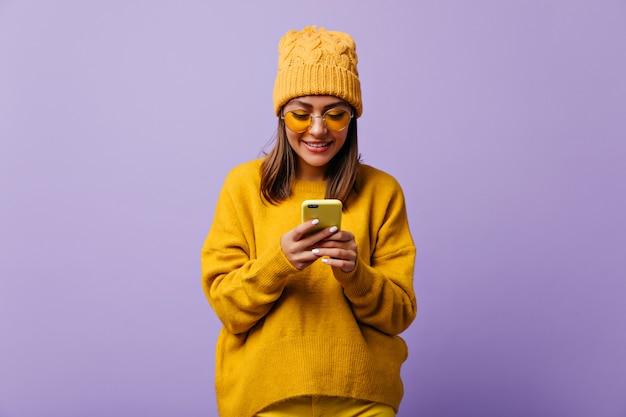 사랑스러운 기쁜 여자는 노란색을 좋아하고 총 노란색 옷을 입는다. 그녀의 스마트 폰에서 채팅하는 아름 다운 여자의 snapportrait