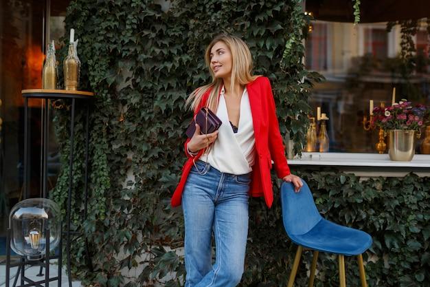 街のカフェでポーズをとって赤いジャケットで素敵な格好良い金髪の女性