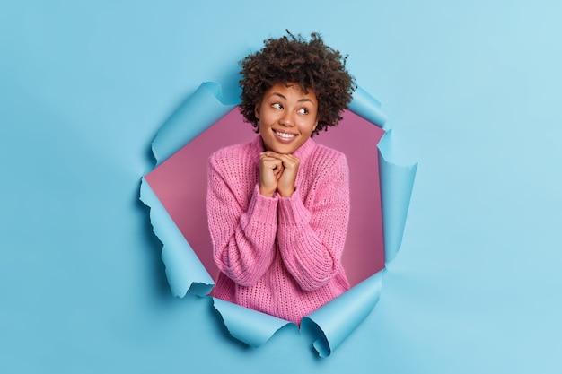 사랑스러운 좋은 찾고 젊은 여자는 턱 미소 아래에 손을 유지 뭔가에 대해 긍정적으로 생각합니다
