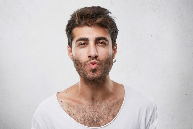 Lovely handsome guy flirting with girl blowing her kiss. unshaved man with attractive appearance showing to his girlfriend sympathy going to kiss her. macho man