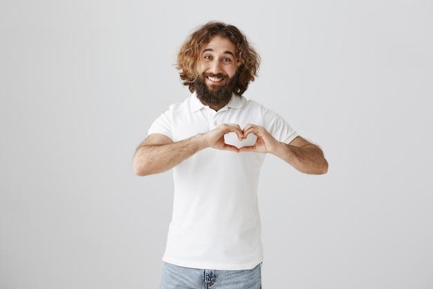 心のジェスチャーを示し、笑みを浮かべて素敵なハンサムな中東男