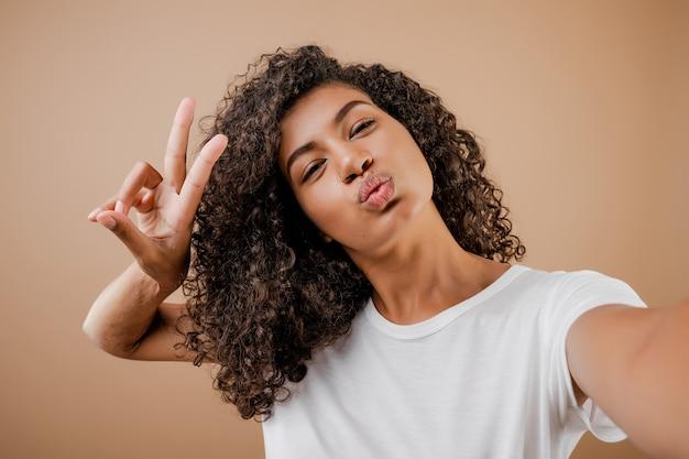 茶色で分離されたselfieを作る素敵な幸せな黒若い女性