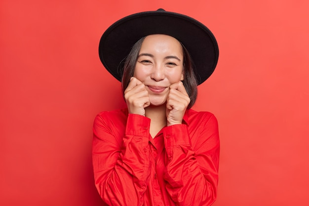 素敵な幸せなブルネットのアジアの女性は頬に手を置いて笑顔を心から持っています柔らかく健康な肌はファッショナブルな黒い帽子をかぶっています赤いシャツは屋内でポーズをとります。心地よい人間の感情と表情