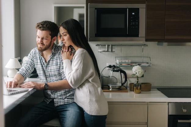 사랑스러운 행복한 커플이 창가에 있는 부엌에서 노트북을 사용하고 있습니다