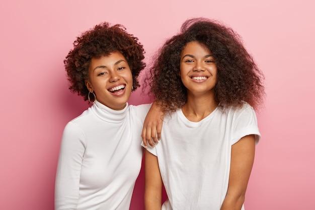 素敵な幸せな暗い肌の女性は一緒に楽しんで、暇な時間を楽しんで、幸せに笑う