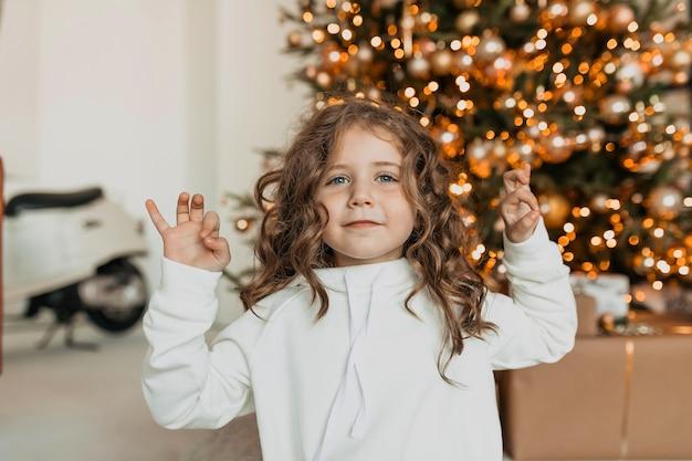 Bella bambina felice con riccioli vestiti di bianco maglia vestiti mani in alto e sorridente davanti all'albero di natale