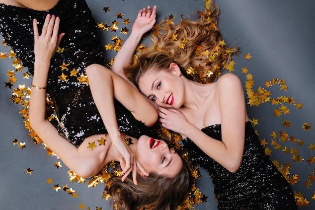 金色の見掛け倒しに横たわっている2人の魅力的な若い女性の上からの素敵な幸せな瞬間。豪華な黒のドレス、笑顔、誕生日パーティー、新年、楽しんで、真のポジティブな感情。