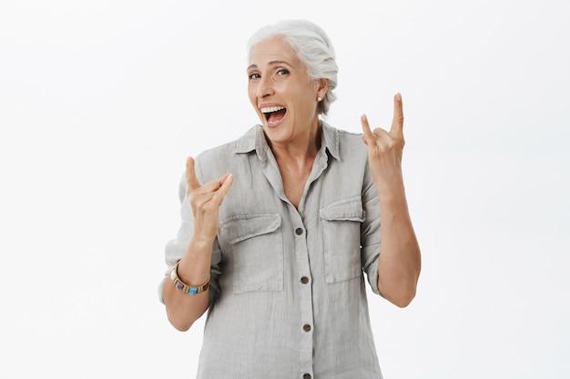 コンサートを楽しんで、ロックンロールジェスチャーを示す素敵な幸せな年配の女性