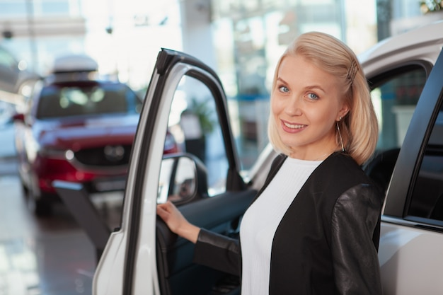 Lovely happy woman smiling joyfully, buying new car at the dealership, copy space
