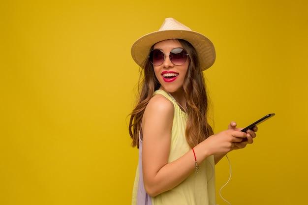 Прекрасная счастливая женщина с длинными темными волосами в шляпе и летнем платье позирует