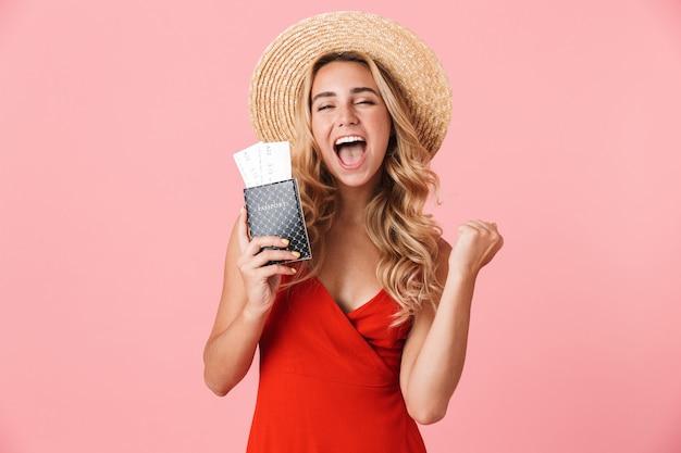 여름 드레스를 입은 사랑스러운 행복한 젊은 금발 여성이 분홍색 벽에 고립되어 서 있고, 비행기 티켓이 있는 여권을 보여주고, 축하합니다.