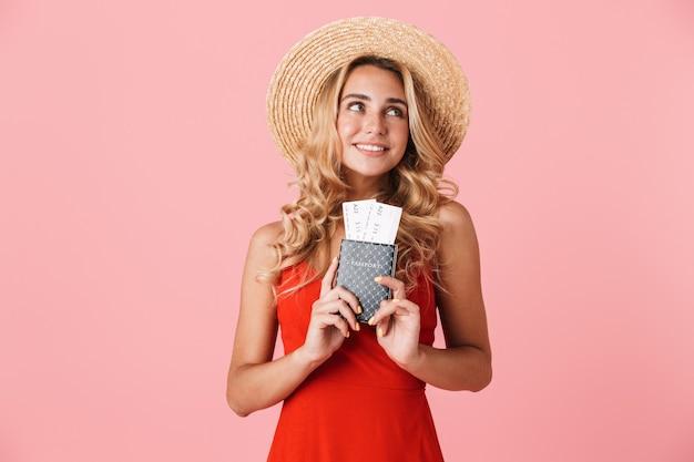 분홍색 벽 위에 고립된 여름 드레스를 입은 사랑스러운 행복한 젊은 금발 여성, 비행기표가 있는 여권을 보여줍니다