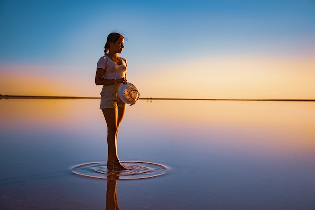 Lovely happy young girl walking along the mirror pink salt lake enjoying the warm evening sun looking at the fiery sunset and her reflection