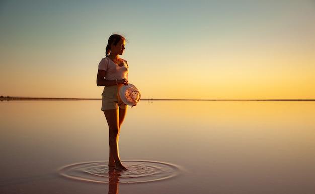Прекрасная счастливая молодая девушка гуляет по зеркальному розовому соленому озеру, наслаждаясь теплым вечерним солнцем, глядя на огненный закат и свое отражение