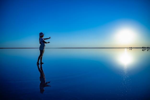 사랑스러운 행복한 어린 소녀는 불타는 석양과 그녀의 반사를 바라보며 따뜻한 저녁 태양을 즐기는 거울 분홍색 소금 호수를 따라 마법의 포즈로 걷고 포즈를 취합니다.