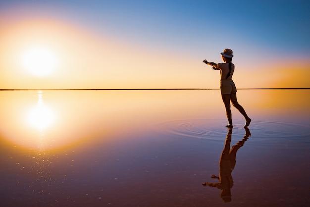 Прекрасная счастливая молодая девушка ходит и позирует в волшебной позе вдоль зеркального розового соленого озера, наслаждаясь теплым вечерним солнцем, глядя на огненный закат и свое отражение