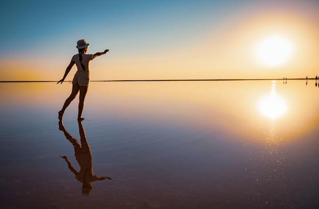 Милая счастливая молодая девушка ходит и позирует в волшебной позе у зеркала розового соленого озера