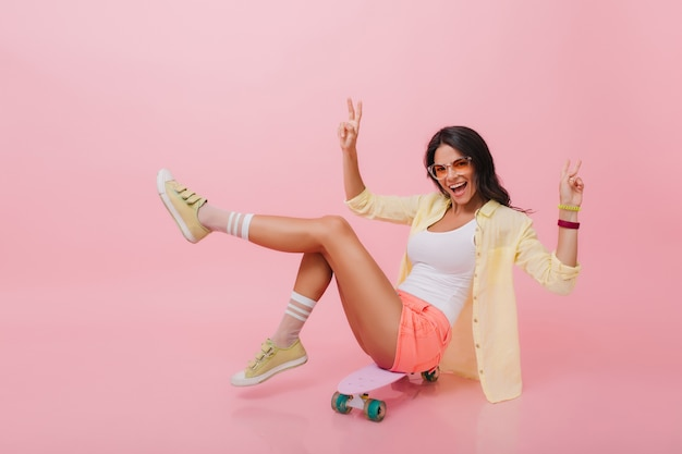 屋内の夏の間に楽しんでいるデニムのショートパンツでブロンズの肌を持つ素敵なヒスパニック系の女性。自由な時間を過ごすロングボードを持つ格好良いアジアの女の子。