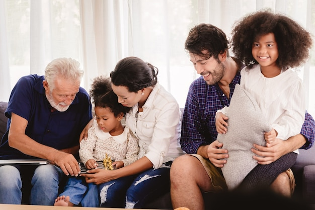 Lovely home happy family living together in living room father mother and grandfather playing with daughter mix race.