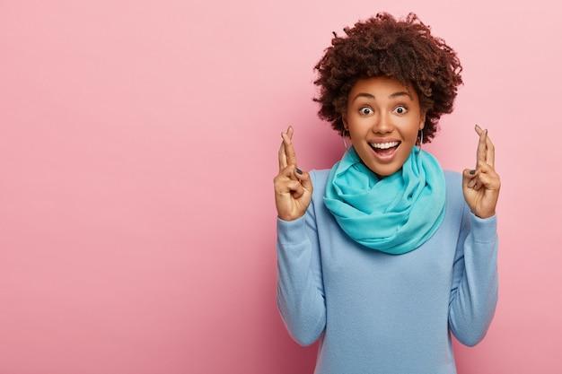 La bella e speranzosa giovane donna afroamericana incrocia le dita per porta fortuna, crede che i sogni si avverino, indossa abiti casual blu, soleggiata sul muro rosa dello studio.