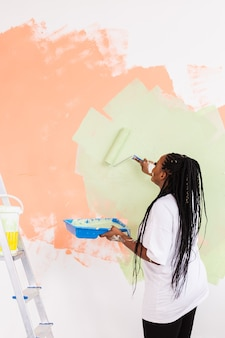 Lovely housewife painting wall