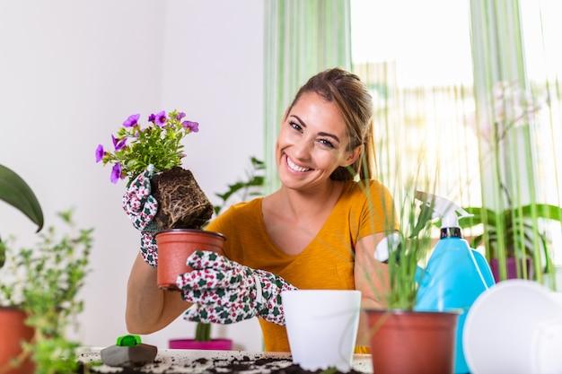 鍋とガーデニングセットで花を持つ素敵な主婦。主婦は植物のために地面を変えます。鉢植えのお手入れ